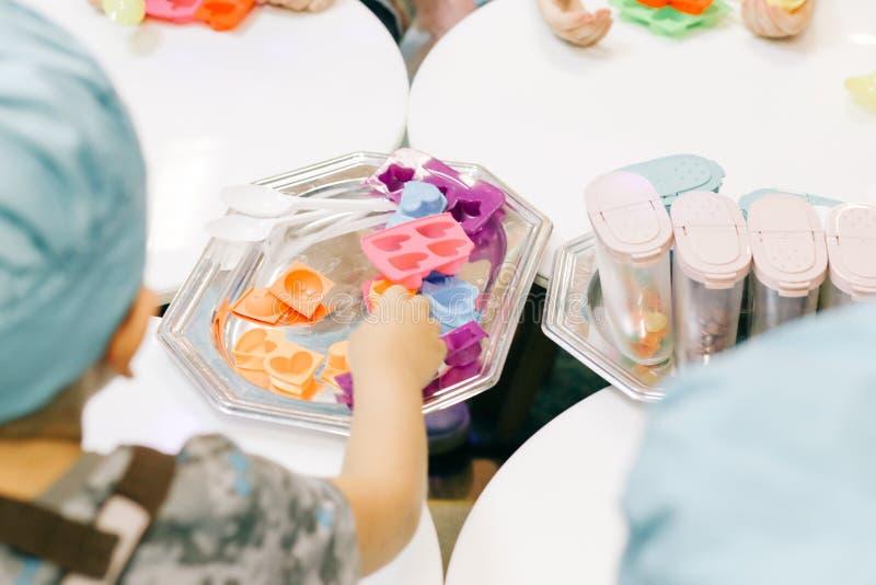 Manos de un niño, de una clase principal en cocinar el chocolate, de la fruta plegable y del chocolate en moldes fotografía de archivo libre de regalías