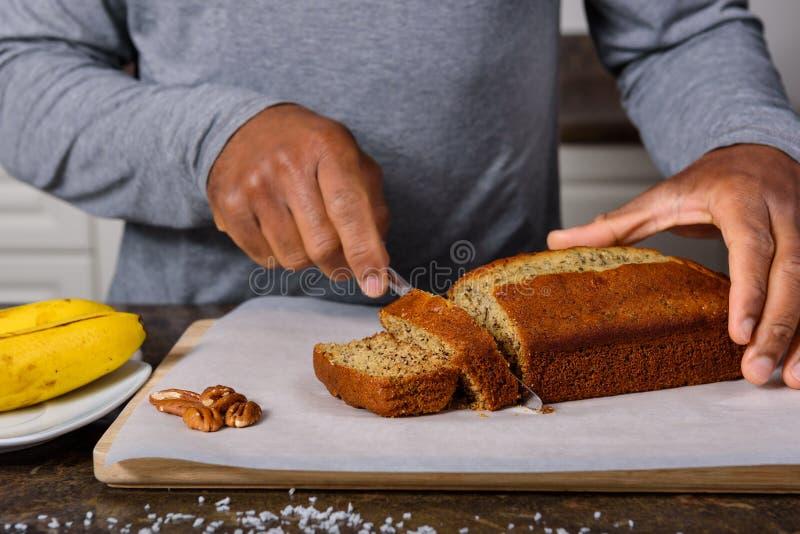 Manos de un pan de plátano del corte del hombre imágenes de archivo libres de regalías