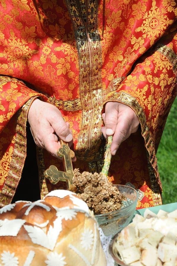 Manos de un sacerdote que sostiene una cruz y una albahaca para bendecir gente y la comida foto de archivo