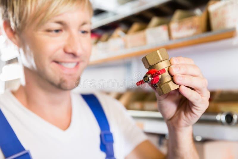 Manos de un trabajador que sostiene dos accesorios de la instalación de tuberías en una tienda sanitaria fotos de archivo libres de regalías