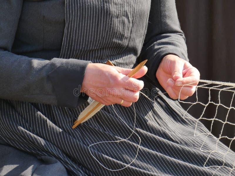 Manos de una esposa del ` s del pescador que teje una nueva red de pesca para los pescados, ropa tradicional, imágenes de archivo libres de regalías