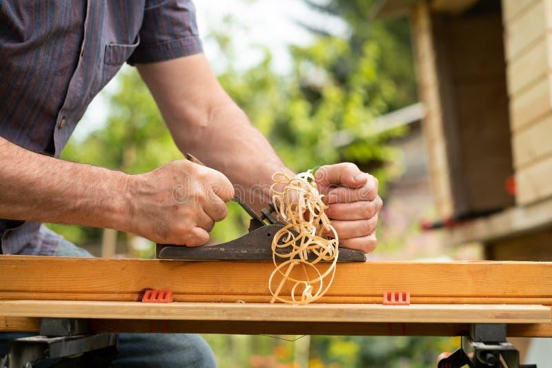 Manos de una madera prevista carpintero al aire libre en verano imagen de archivo