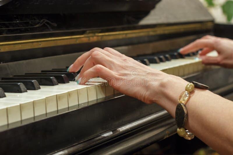 Manos de una muchacha que juega en un piano blanco, primer imagen de archivo libre de regalías