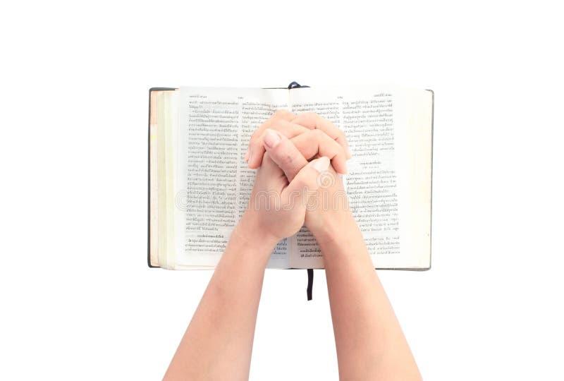 Manos de una mujer irreconocible con la biblia que ruega en el CCB blanco imagen de archivo