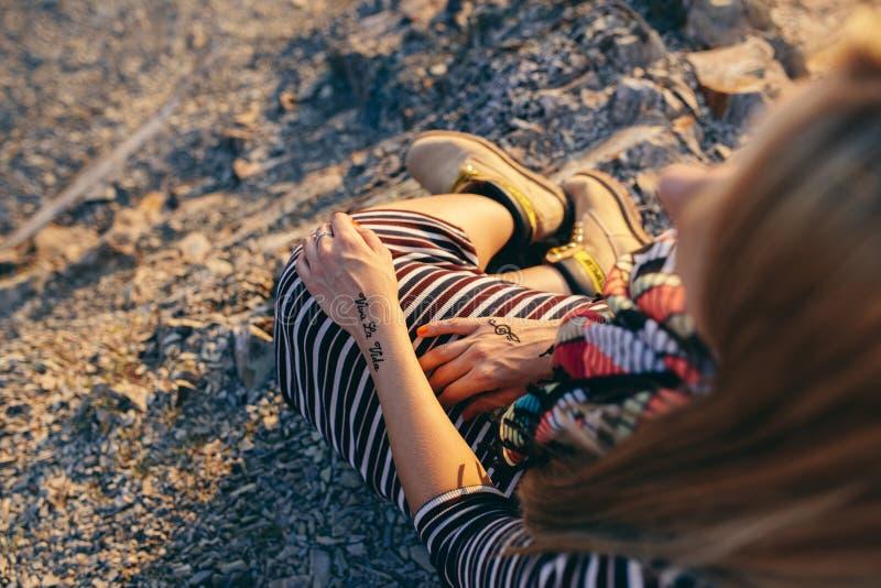 Manos de una mujer joven en un vestido rayado, una bufanda colorida y botas amarillas con el ` y el triple de Viva la Vida del `  imagen de archivo libre de regalías