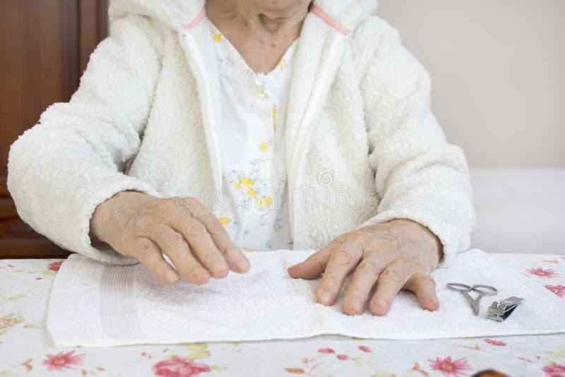 Manos de una mujer mayor preparada para un tratamiento cosmético fotografía de archivo