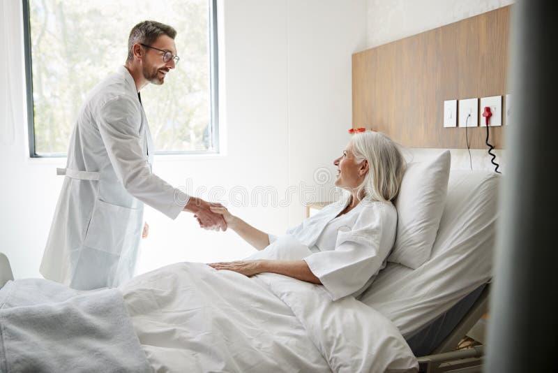 Manos de Visiting And Shaking del cirujano con el paciente femenino maduro en cama de hospital imágenes de archivo libres de regalías