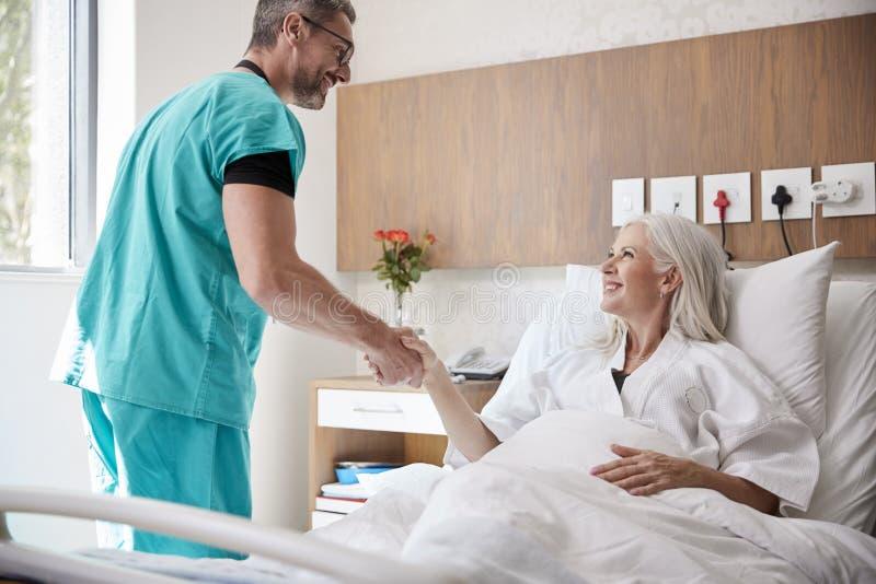 Manos de Visiting And Shaking del cirujano con el paciente femenino maduro en cama de hospital foto de archivo