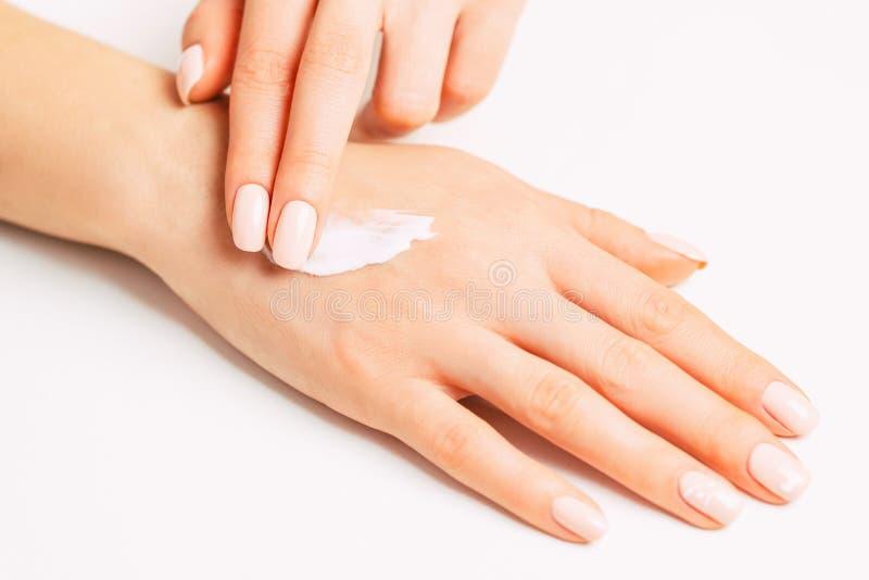 Manos de Woman's que aplican la crema hidratante del skincare fotografía de archivo
