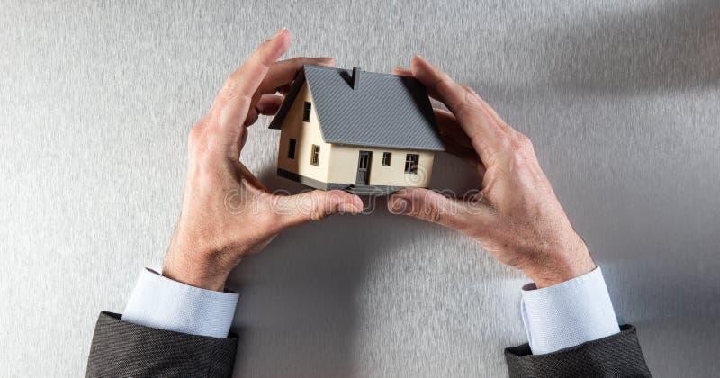 Manos del arquitecto o del hombre de negocios que sostiene la casa para la evaluación casera imagen de archivo