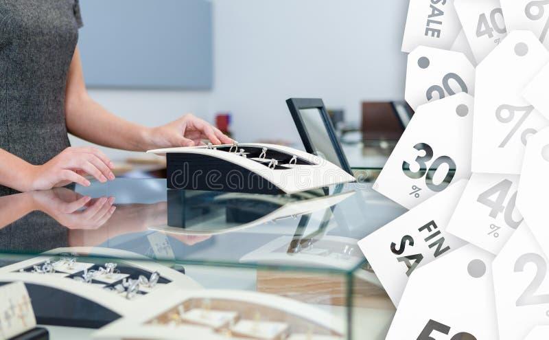 Manos del ayudante de la compensación en la caja de ventana con los anillos de diamante fotografía de archivo