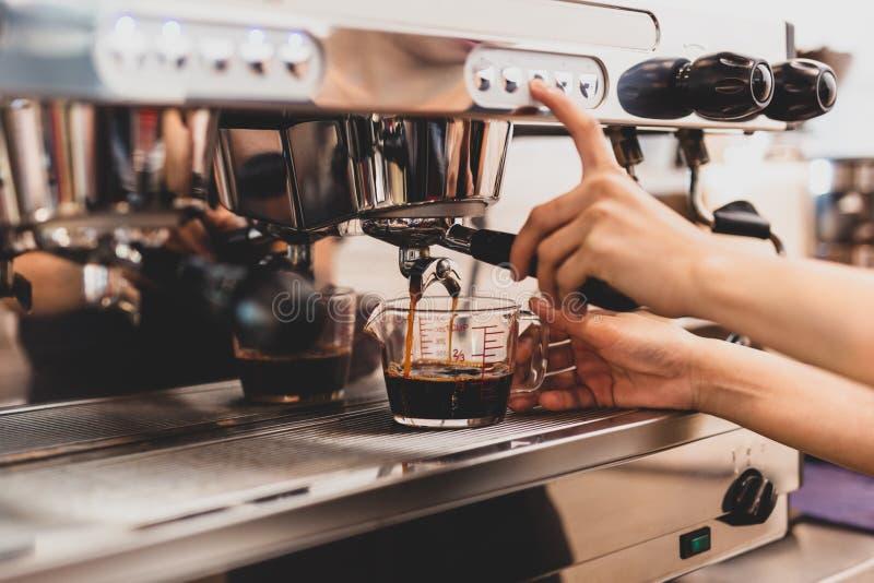 Manos del barista femenino que presionan el botón en la máquina mientras que hace el café fresco fotografía de archivo
