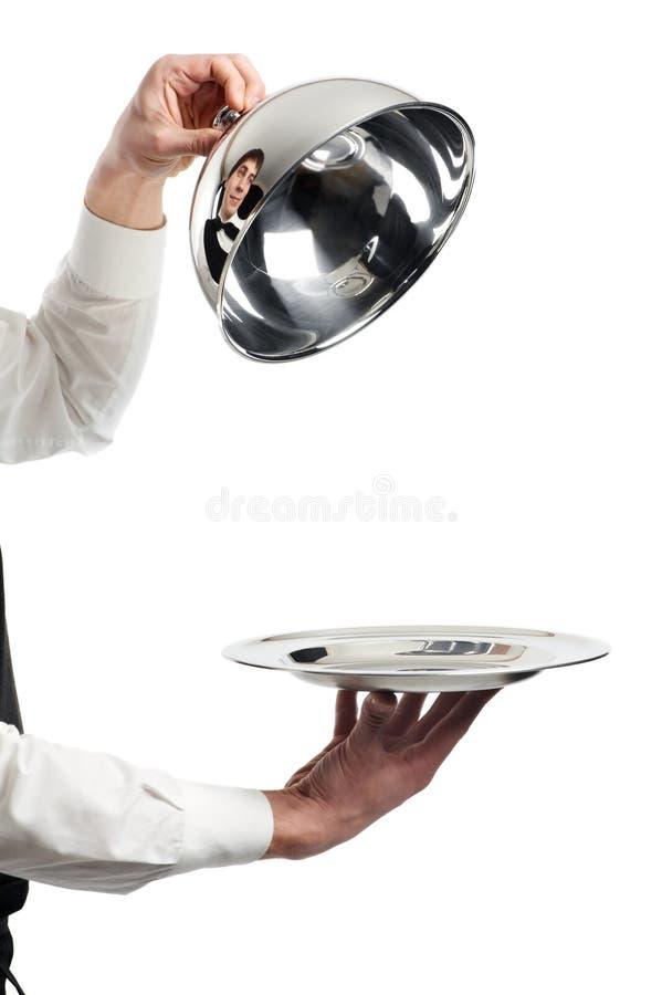 Manos del camarero con la tapa del cloche foto de archivo