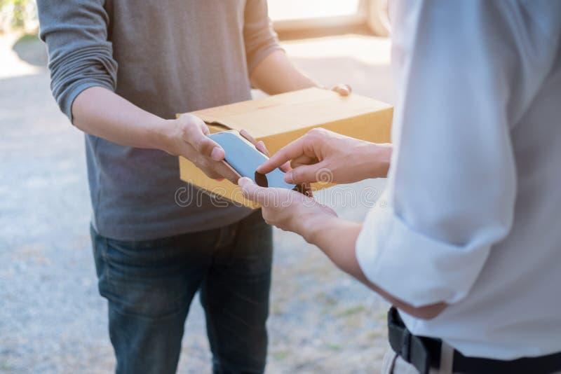 Manos del cliente que añaden la firma en el teléfono móvil, hombre que recibe la caja del paquete postal de mensajero con el homb imagenes de archivo