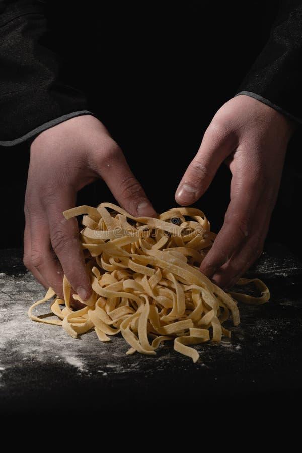 Manos del cocinero que hacen los espaguetis, pastas, tallarines con las pastas frescas en la tabla negra con fotos de archivo libres de regalías