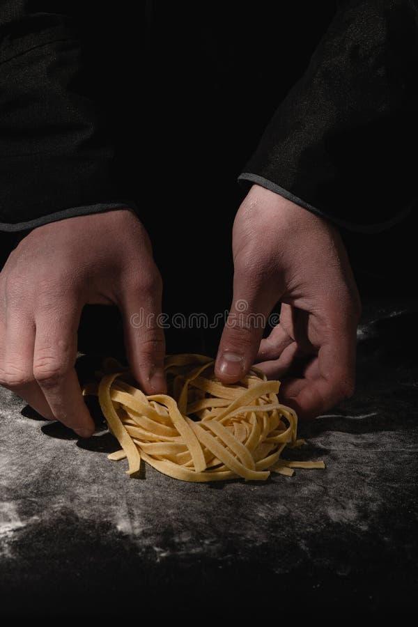 Manos del cocinero que hacen los espaguetis, pastas, tallarines con las pastas frescas en la tabla negra con imagen de archivo libre de regalías