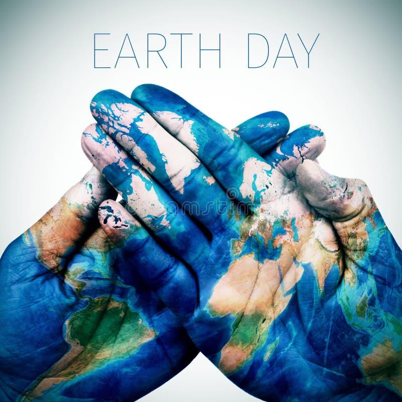 Manos del Día de la Tierra y del hombre del texto modeladas con un mapa del mundo (suministre foto de archivo libre de regalías