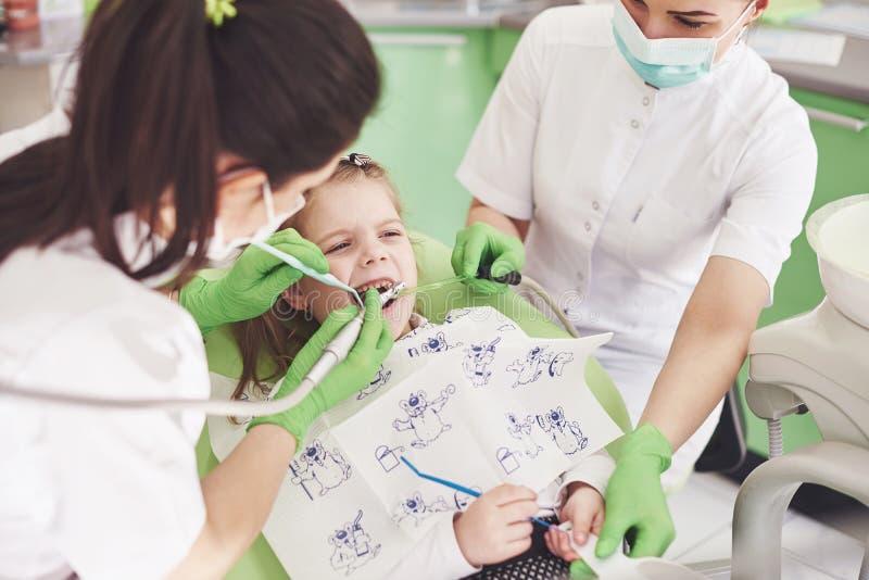 Manos del dentista pediátrico irreconocible y del procedimiento de fabricación auxiliar del examen para la niña linda sonriente imagenes de archivo