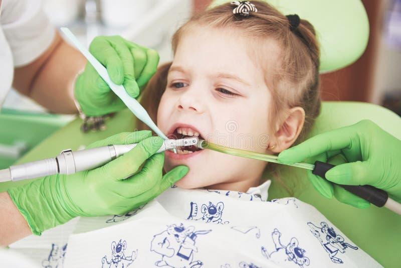 Manos del dentista pediátrico irreconocible y del procedimiento de fabricación auxiliar del examen para la niña linda sonriente fotografía de archivo