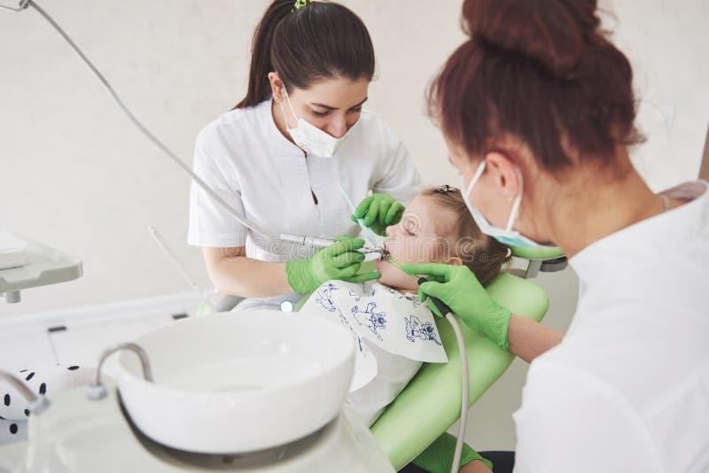 Manos del dentista pediátrico irreconocible y del procedimiento de fabricación auxiliar del examen para la niña linda sonriente fotografía de archivo libre de regalías