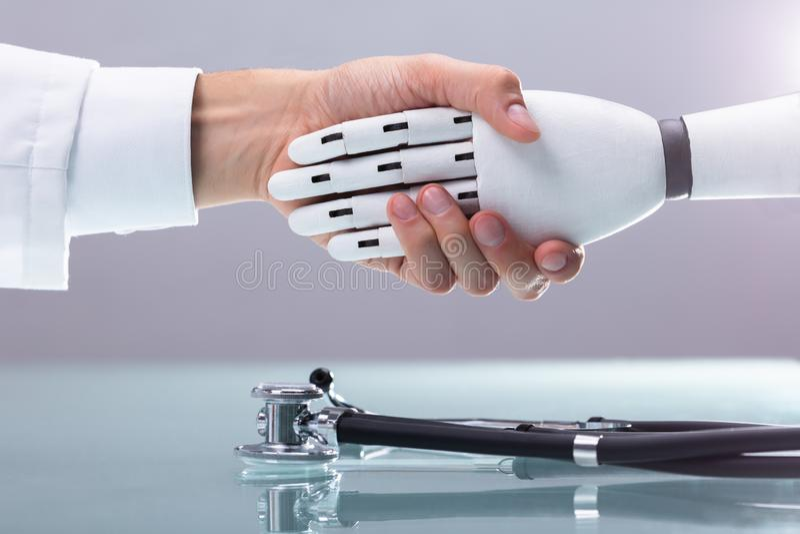 Manos del doctor And Robot Shaking fotos de archivo