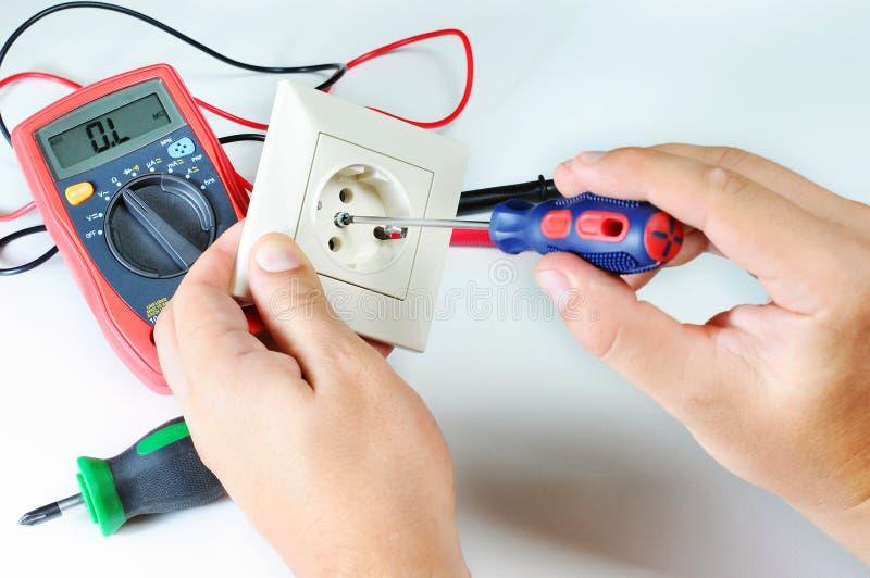 Manos del electricista con el zócalo electricidad y concepto de la gente Multímetro de Digitaces Destornillador fotografía de archivo libre de regalías