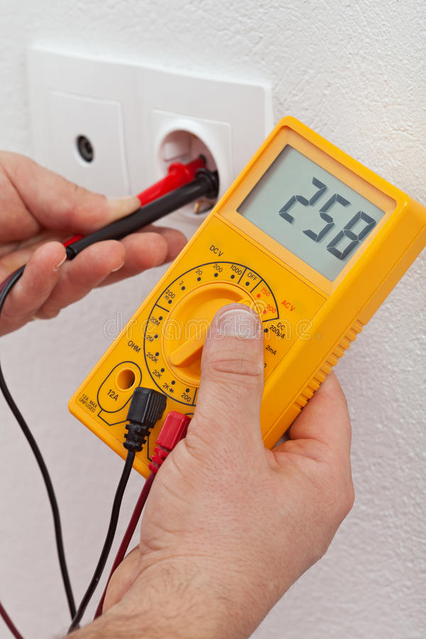 Manos del electricista que miden voltaje en mercado eléctrico foto de archivo libre de regalías