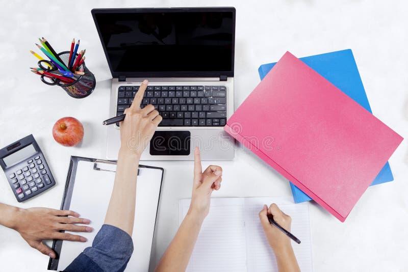 Manos del estudiante que señalan en la pantalla del ordenador portátil foto de archivo libre de regalías
