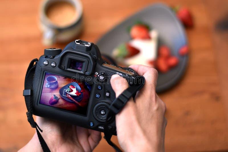 Manos del fotógrafo que sostienen la cámara del dslr que toma una foto de un postre de la fresa fotografía de archivo libre de regalías