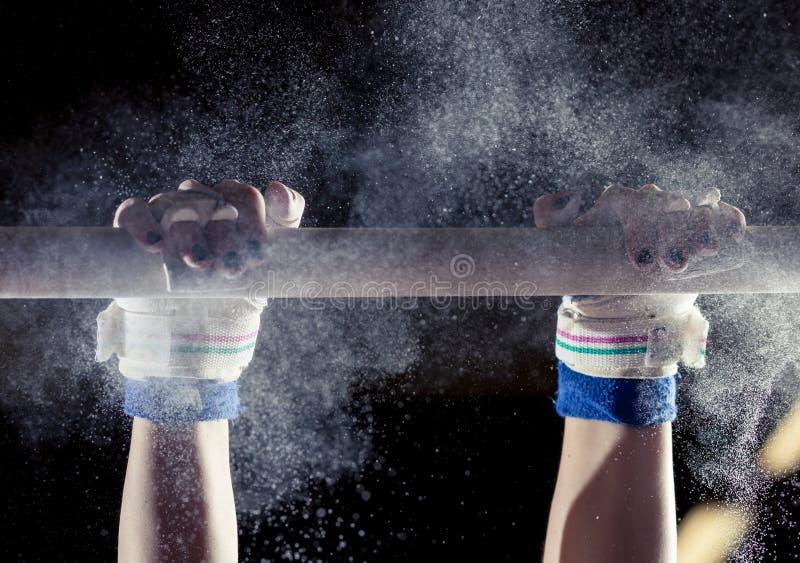 Manos del gimnasta con tiza en barras desiguales foto de archivo