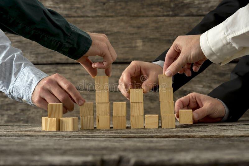 Manos del hombre de negocios cinco que lleva a cabo los bloques de madera que los ponen internacional fotografía de archivo