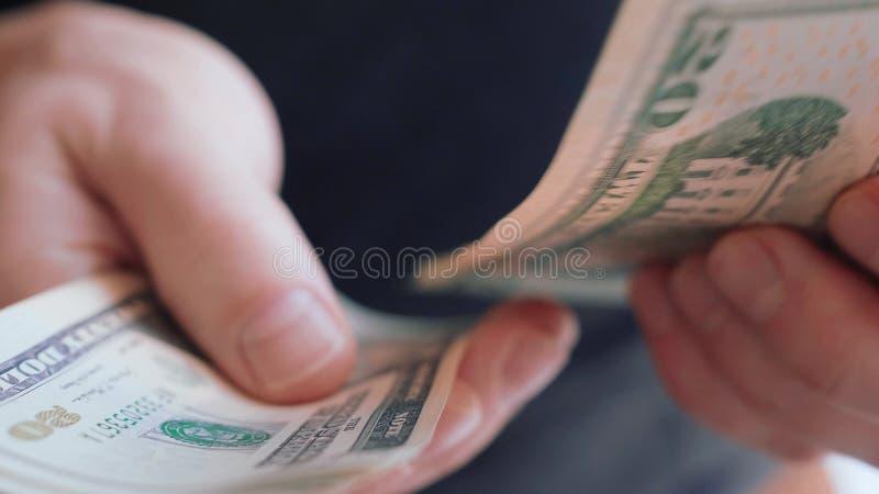 Manos del hombre de negocios que cuentan muchos 20 dólares americanos de cierre de los billetes de banco 4K encima del MES lento fotografía de archivo