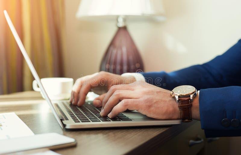 Manos del hombre de negocios que mecanografían en un ordenador portátil fotografía de archivo