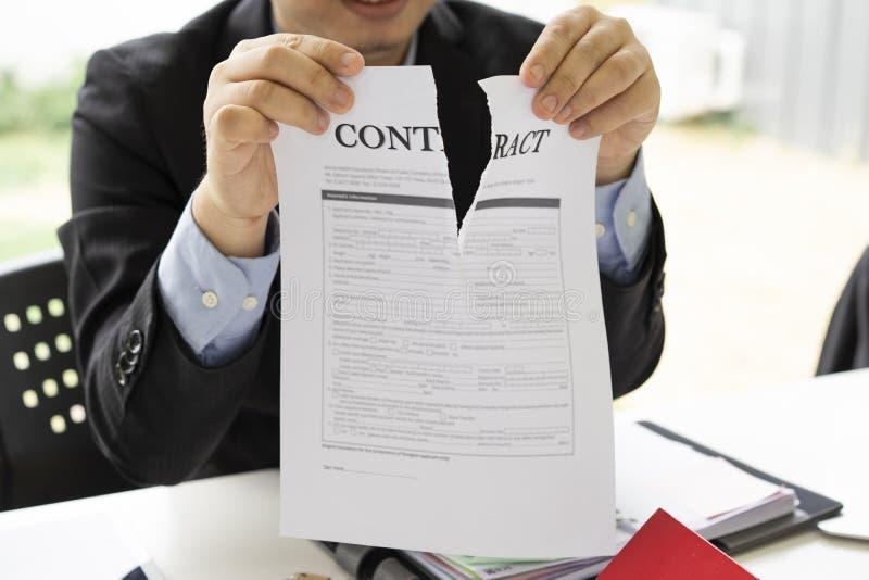 Manos del hombre de negocios que rasgan el papel de acuerdo de contrato, contrato cancelado, imagen de archivo