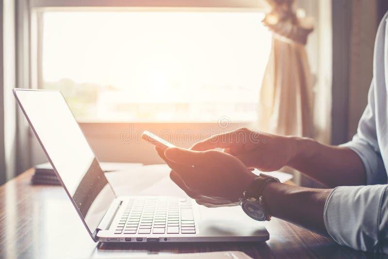 Manos del hombre de negocios usando el teléfono celular con el ordenador portátil en el escritorio de oficina fotografía de archivo libre de regalías
