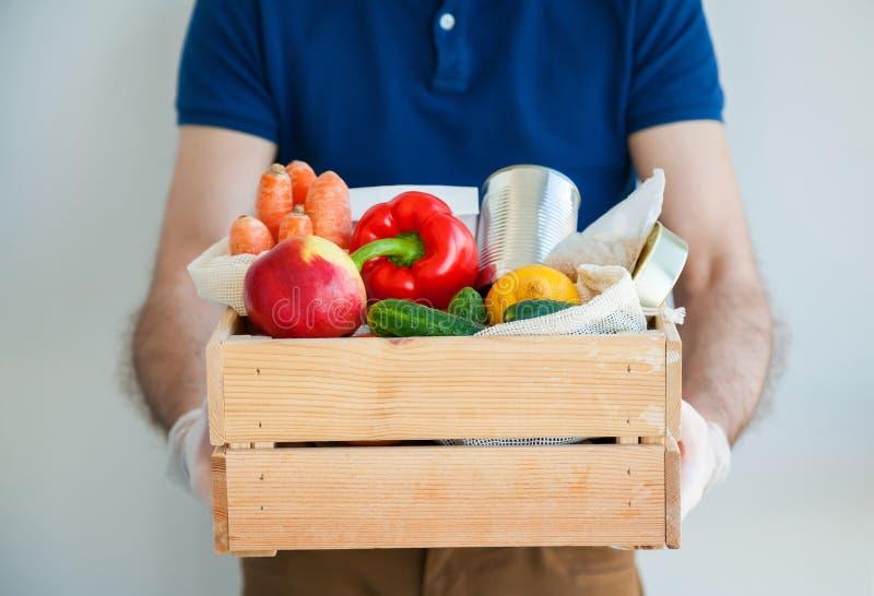 Manos del hombre en guantes sosteniendo la caja de alimentos foto de archivo libre de regalías