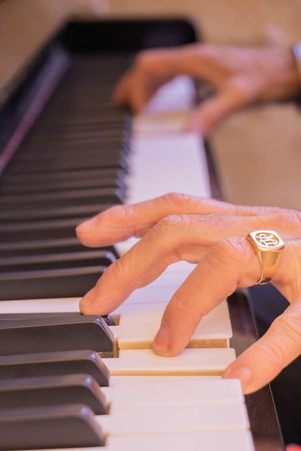 Manos del hombre en las llaves de un piano fotos de archivo