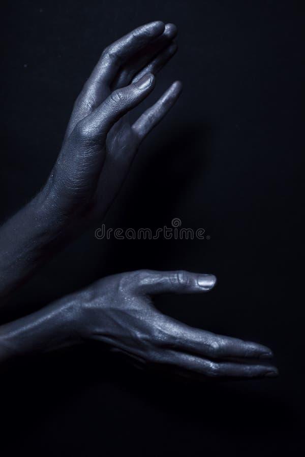 Manos del hombre hermoso en la pintura de plata fotografía de archivo