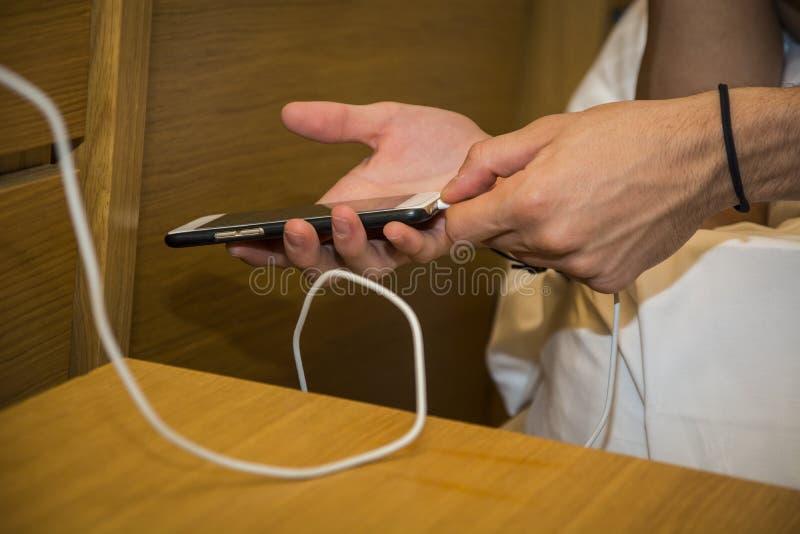Manos del hombre que conectan un teléfono con un cargador por la suya imagen de archivo