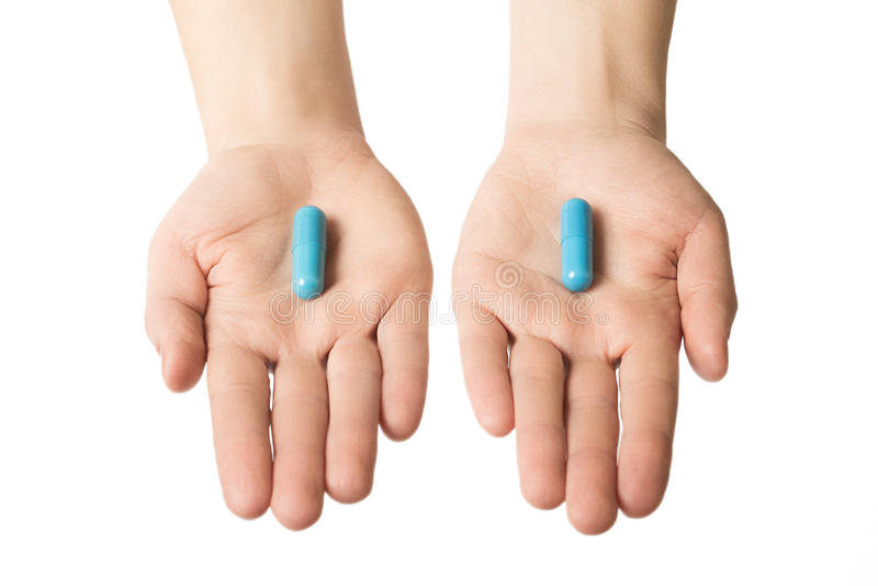 Manos del hombre que dan dos píldoras azules grandes Tome su decisión Concepto tranquilo de los nervios imagenes de archivo