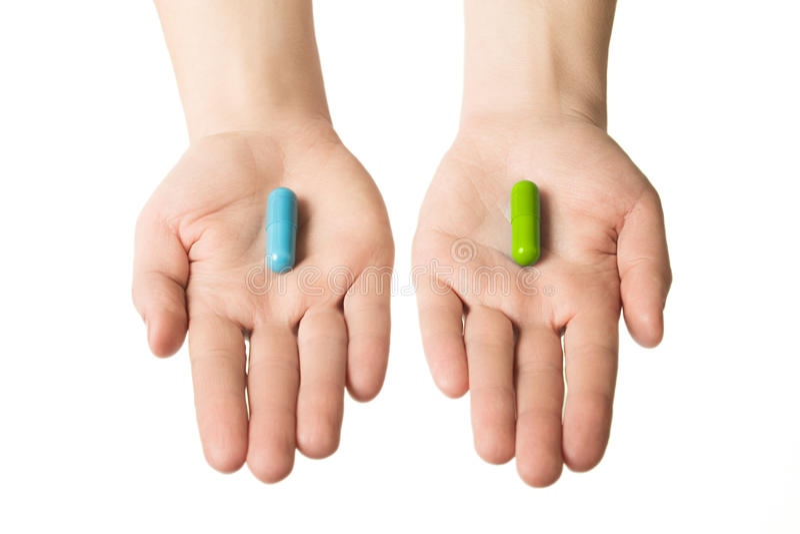 Manos del hombre que dan dos píldoras grandes Azul y verde Haga su selección nervios tranquilos y salud Elija su lado foto de archivo libre de regalías