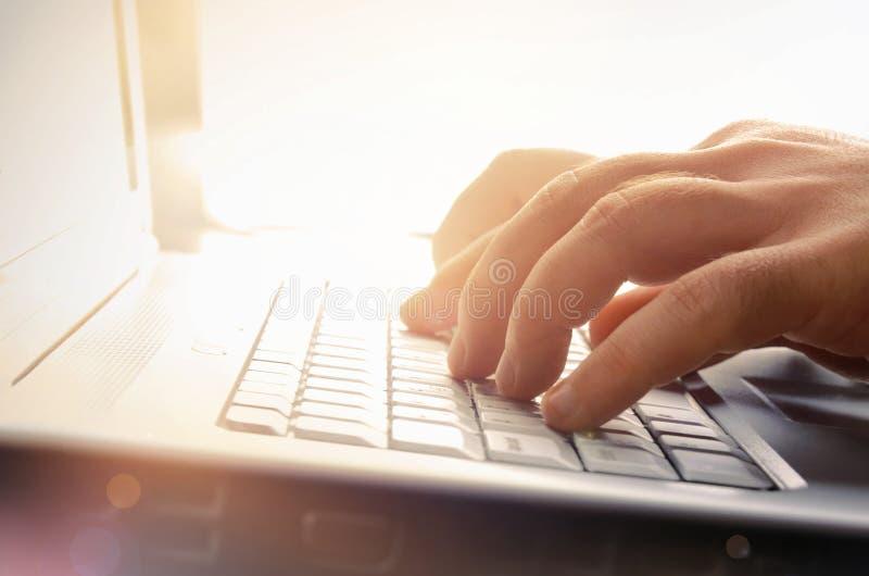 Manos del hombre que pulsan en el teclado de la computadora portátil foto de archivo