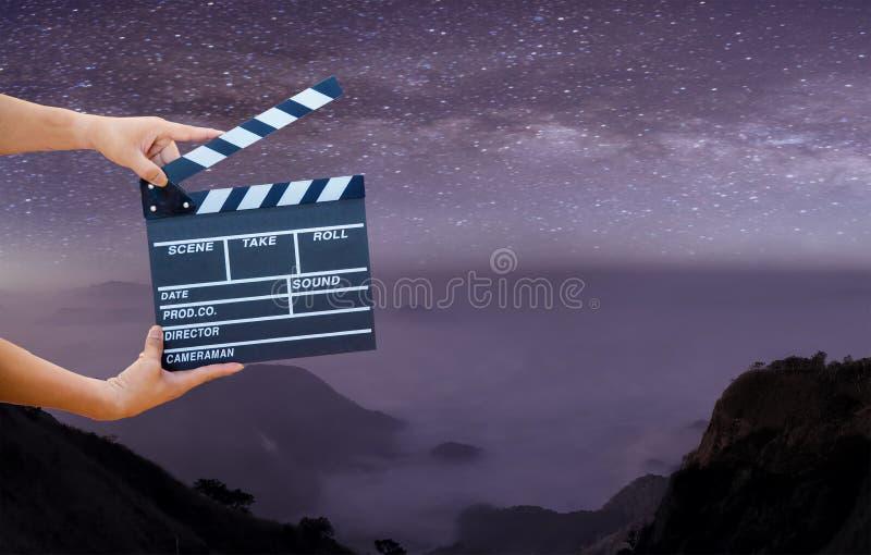 Manos del hombre que sostienen la chapaleta de la película en vía láctea, las estrellas y las montañas Tablero mostrado de la piz libre illustration