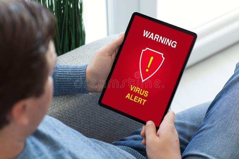 Manos del hombre que sostienen la tableta con la alarma de cuidado de la alarma del virus imágenes de archivo libres de regalías