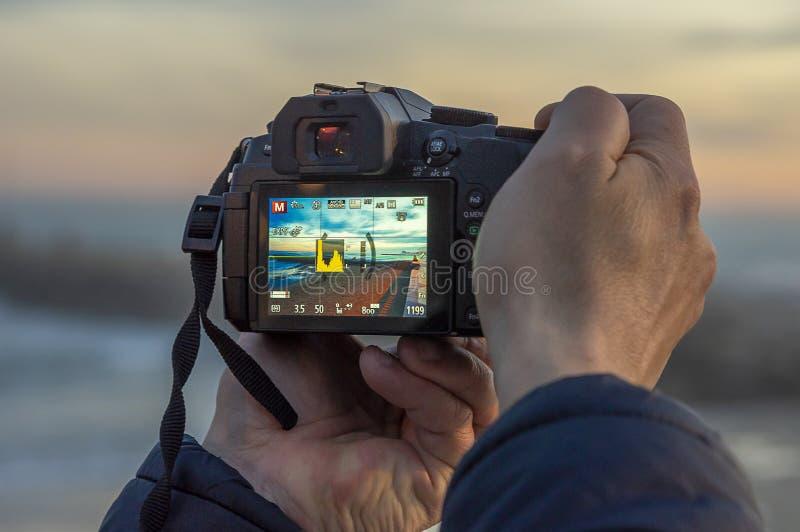 Manos del hombre que toman una fotografía con DSLR del paisaje de la puesta del sol foto de archivo