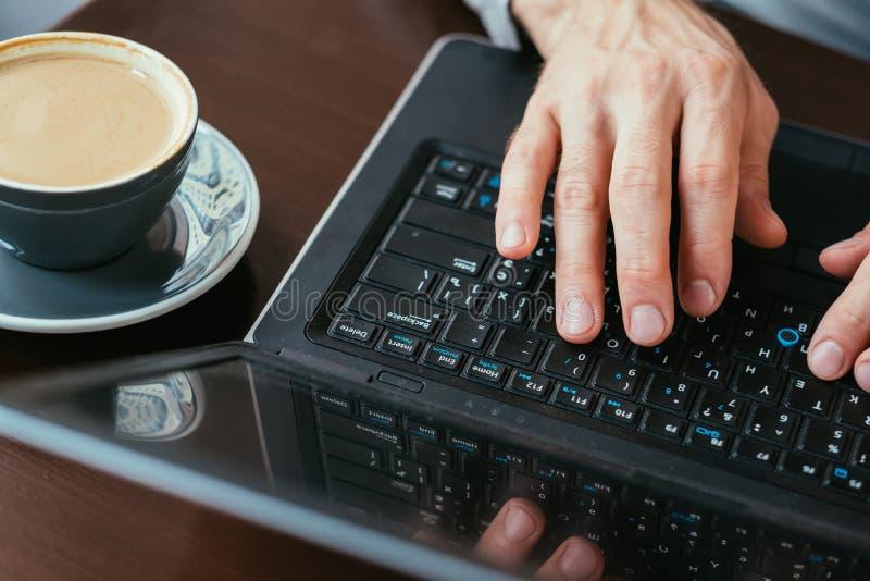Manos del hombre del trabajo del descanso para tomar café que mecanografían la taza del ordenador portátil imagenes de archivo