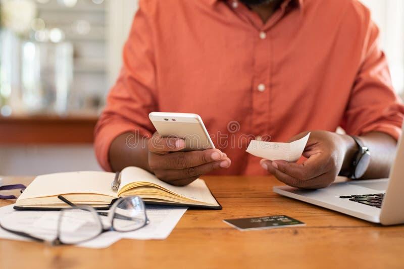 Manos del hombre usando recibo del smartphone y el sostenerse fotos de archivo libres de regalías