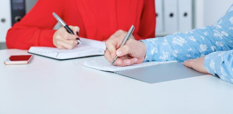 Manos del hombre y de la mujer que escriben la letra, lista, plan, haciendo las notas, haciendo el primer de la preparación Educa imagenes de archivo