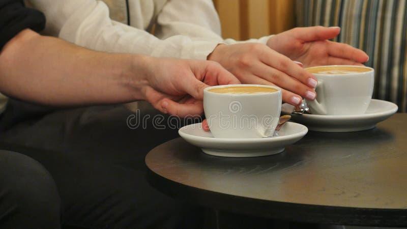 Manos del hombre y de la mujer que sostienen las tazas con café fotos de archivo libres de regalías