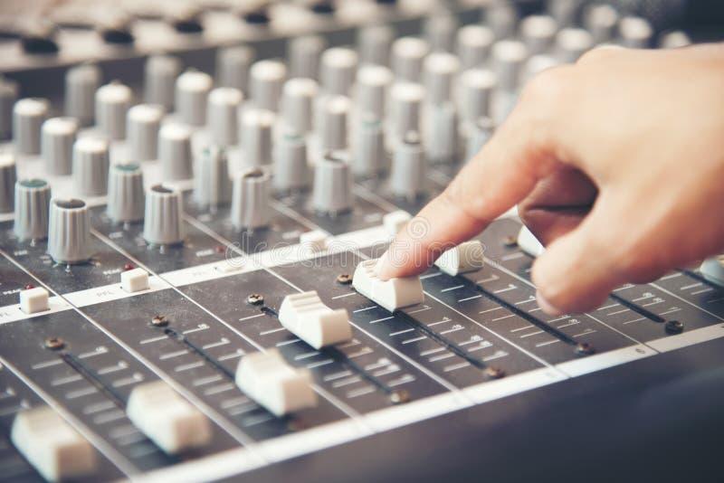 Manos del ingeniero de sonido que trabajan en mezclador del estudio de grabación Experto que ajusta el volumen de una voz, consol foto de archivo libre de regalías
